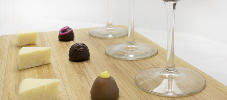 small cheese wedges on a board with chocolate truffles and wine glasses