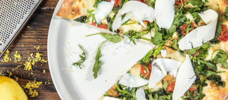 pizza with herbs, tomatoes, and cheese on a plate