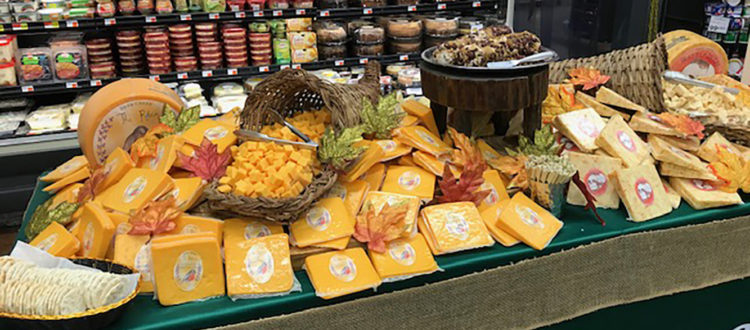 Large Table set up with variety of cheeses in a grocery store